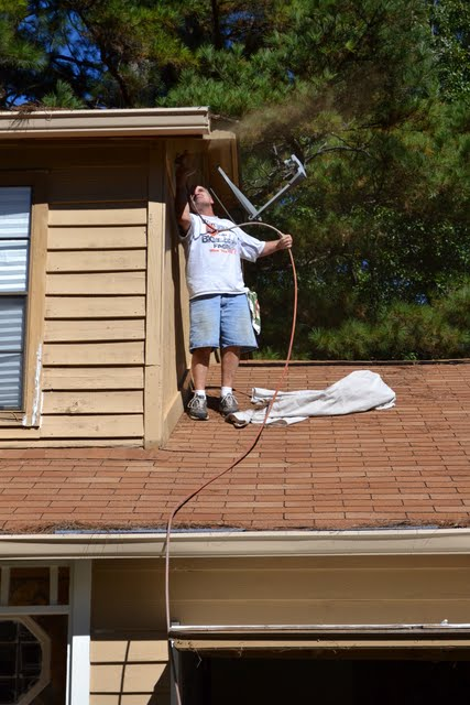 painting the house tan using sprayer on the roof