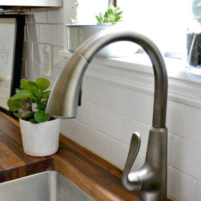 closeup of faucet next to butcher block