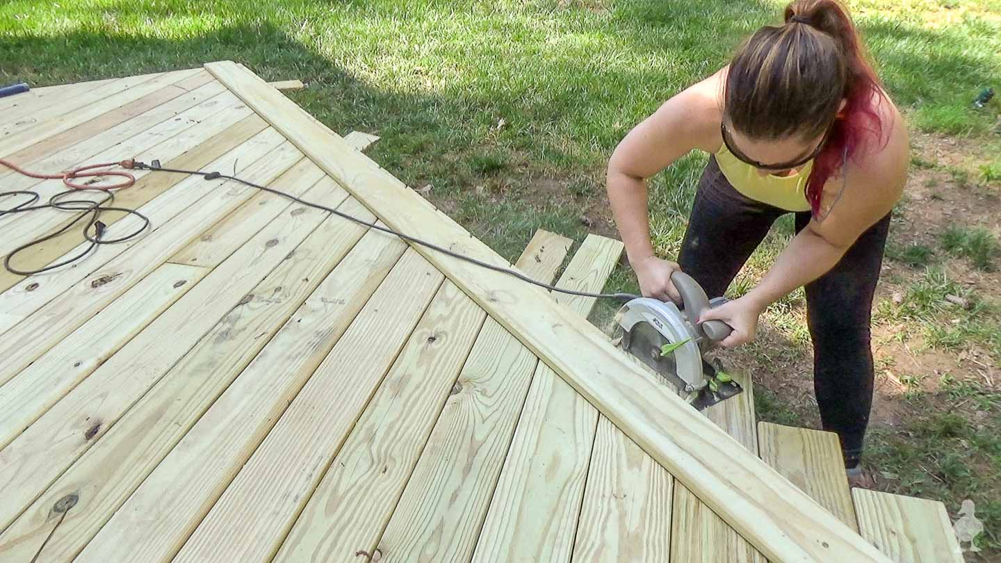 woman (me) trimming off end of deck boards