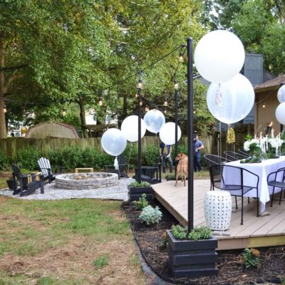 backyard with floating deck fire pit and hanging outdoor lights