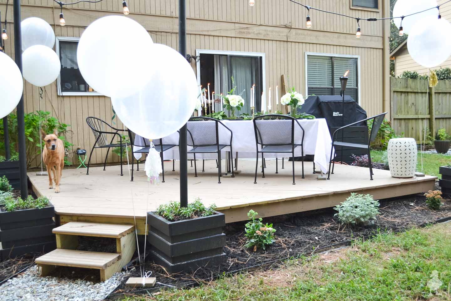 tan floating deck in back yard with white balloons and black chairs