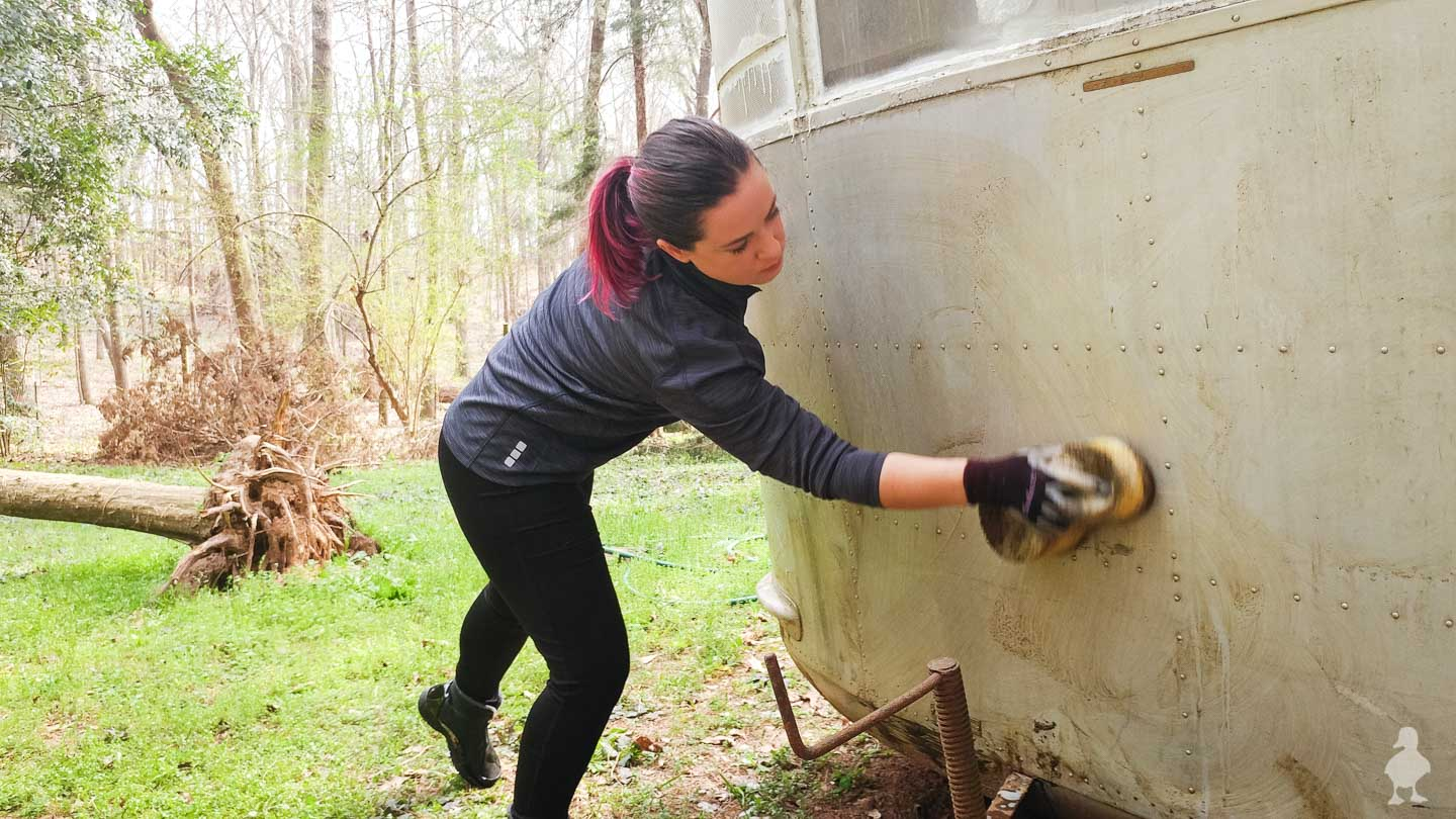 me scrubbing down the front of the vintage travel trailer