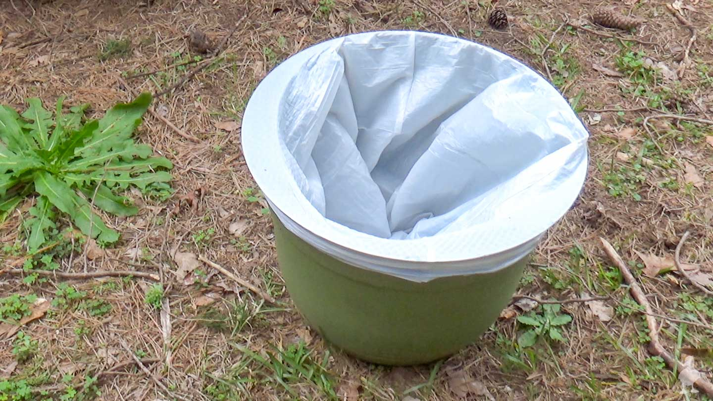 planter with garbage bag used as a water bucket for car wash soap
