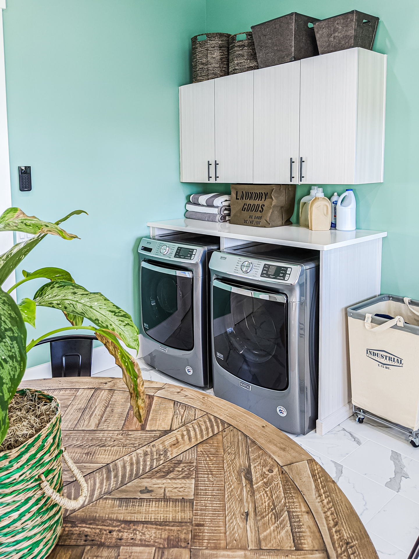 mudroom laundry room with teal walls and marble floor