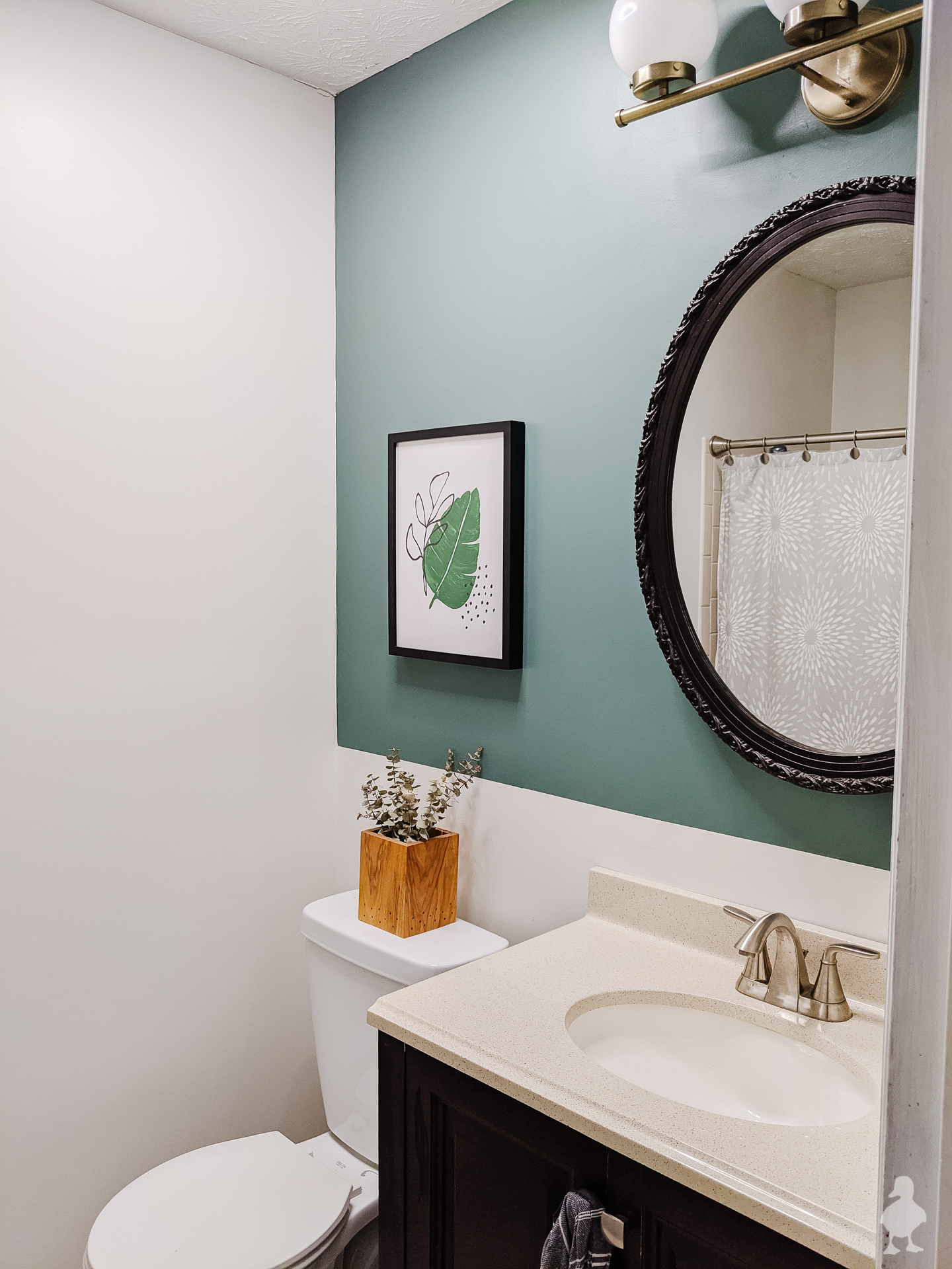 bathroom makeover featuring nature inspired calm green accent wall